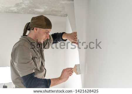 Young repairman smear on wall glue with a brush. Worker glueing wallpapers on concrete wall. Repair the apartment. Home renovation concept. White Wallpaper for paint #1421628425