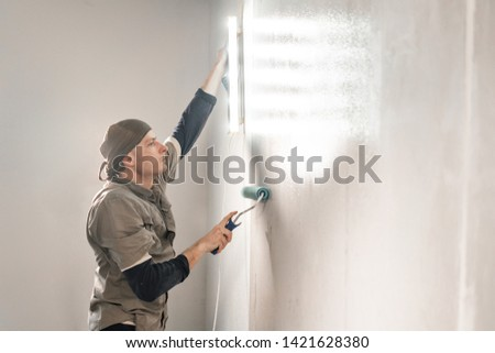 Young repairman smear on wall glue with a roller. . Worker glueing wallpapers on concrete wall. Repair the apartment. Home renovation concept. White Wallpaper for paint
