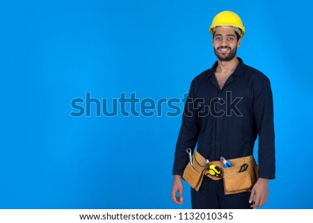Young repairman standing confidently wears overalls-wearing smiling on a blue background. #1132010345