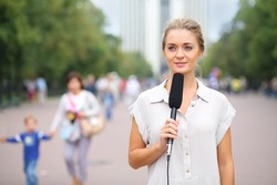 Young reporter standing in the street with a microphone in her hand and looking away