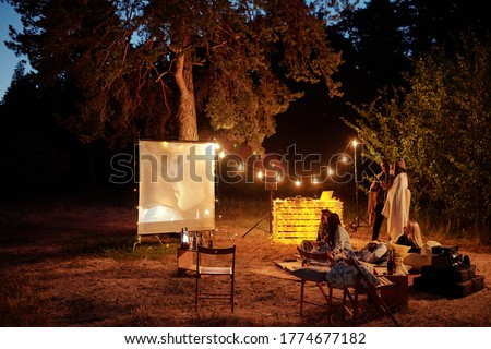 Young restful friends having drinks and watching movie on white screen in the evening in natural environment while sitting on the ground