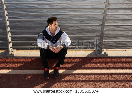 Young restful sportsman in activewear sitting by riverside while enjoying music in airpods after training outdoors #1395505874