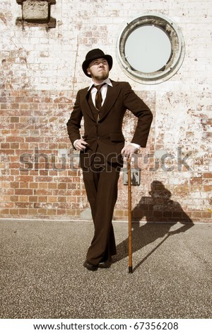 Young Retro Gentleman In Suit, Bowler Hat And Walking Stick With Brick Wall Background