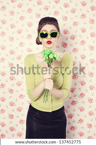 young retro style lady holding green roses like microphone and singing in front of retro wall background