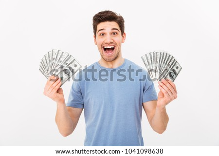Young rich man in casual t-shirt holding two fans of money dollar bills with surprise isolated over white wall