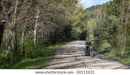 Young rider driving his cruiser-type motorcycle on the forest road.