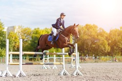 Young rider girl performing jump at horse show jumping competition. Equestrian sport background