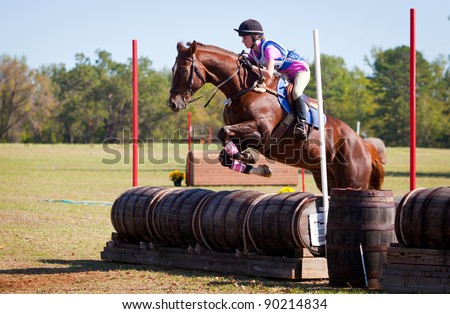 Young rider jumps over barrels on a cross country eventing course.