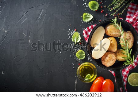 Young ripe potatoes in a black cast iron pan with herbs, olive oil, rosemary, pepper, sea salt for baking. Healthy homemade food, Vegetarian and diet
