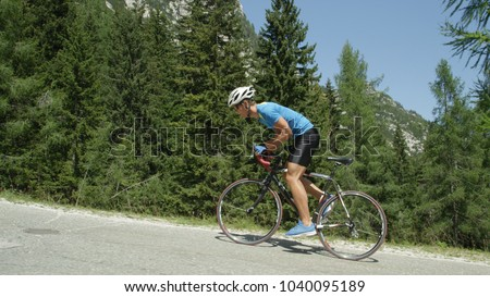 Young road biker guy charges up steep asphalt road towards the finish line. Determined sportsman pedals uphill during exhausting bicycle race in the beautiful mountains. Awesome outdoor exercise. #1040095189