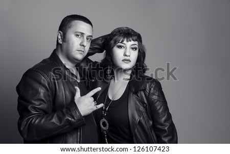 young rocker couple with leather jackets posing and looking at camera
