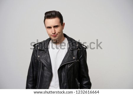 Young rocker, rebel, moto racer with a stylish hairstyle in briolin, tattoo on the neck, looking in the style of 50s-60s in black leather jacket, looks dissatisfied, purses one corner of the lips ストックフォト ©