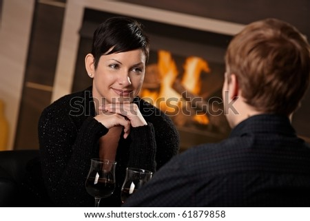 Young romantic couple dating, sitting in front of fireplace at home, drinking red wine.