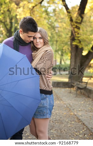 young romantic couple in autumn park embracing