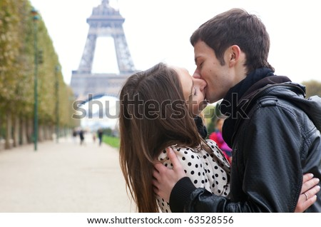 Young romantic couple kissing near the Eiffel Tower in Paris - stock