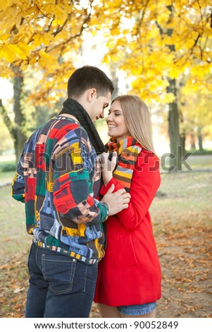 young  romantic  couple kissing under tree in autumn park