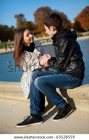 Young romantic couple near water at warm sunny autumn day