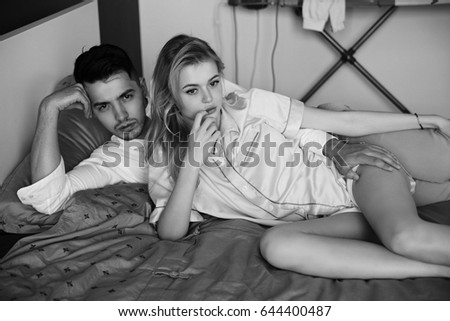 Young romantic couple relaxing and hugging in bed. Pretty beautiful blonde girl and brunette man. Black and white photo. #644400487
