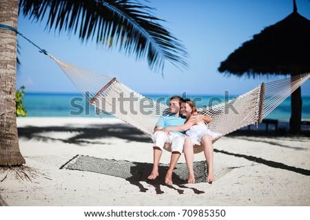 Young romantic couple relaxing in hammock on tropical beach of Zanzibar island