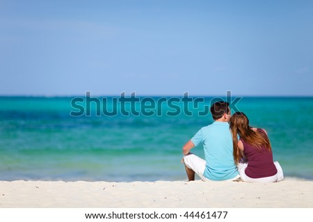 Young romantic couple relaxing on tropical beach of Zanzibar island