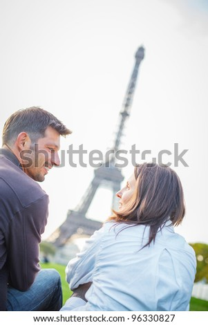 Young romantic couple sitting near the Eiffel Tower in Paris