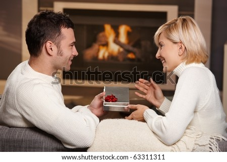 Young romantic couple sitting on couch in front of fireplace at home, man giving gift, side view.