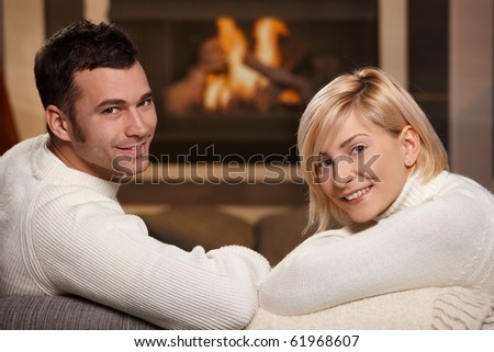 Young romantic couple sitting on sofa in front of fireplace at home, looking back, smiling.