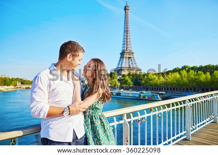 Young romantic couple spending their vacation in Paris, France. Dating couple posing near the Eiffel tower #360225098