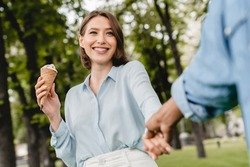 Young romantic couple students friends boyfriend and girlfriend walking in city park spending time together on romantic date eating ice-cream outdoors. Love and relationship, first love, true feelings