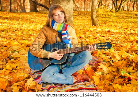 Young romantic girl sitting in autumn park with guitar