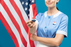 Young room-maid in blue uniform showing you vote insignia while standing against stars-and-stripes flag background
