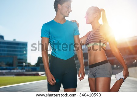 Young runner stretching her legs before a track event. Two young runners on a sunny day practicing at athletics stadium.