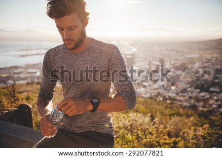 Young runner with a water bottle taking a break after hard running training outdoors. Young man relaxing after a run about to drink water.