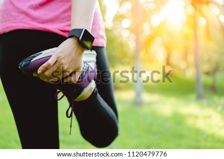 Young runner woman stretching leg before run in park. Close up athletic girl wear running shoes, smart watch warm up outdoor. Sport activity tracker watch at wrist to monitor heart rate during cardio