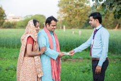Young rural indian couple farmer receive money from banker at agriculture field.