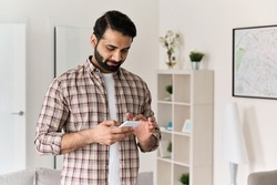 Young 30s indian man holding smartphone tech device using cell phone apps at home. Bearded ethnic guy texting messages looking at smart phone checking social media, ordering online or browsing.