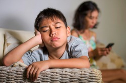 young sad and bored 7 Asian child at home couch feeling frustrated and neglected while mother using mobile phone as internet addict neglecting her son during covid-19 stay home lockdown