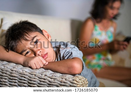 young sad and bored 7 Asian child at home couch feeling frustrated and neglected while mother using mobile phone as internet addict neglecting her son during covid-19 stay home lockdown Stock photo ©