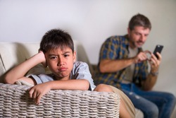 young sad and bored 7 or 8 years old child at home couch feeling frustrated and unattended while man networking on mobile phone as internet addict father neglecting his young son