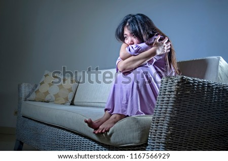 young sad and depressed Asian Japanese woman crying alone desperate and worried in pain sitting at home sofa couch suffering depression and anxiety problem feeling lonely and helpless