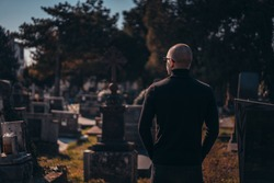 Young sad and serious man in black at the cemetery paying respect at grave and visiting relative commemorating ancestors
