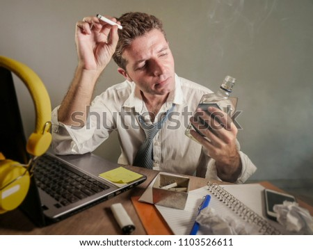 Young Sad And Wasted Messy Business Man Working At Laptop Computer Office Desk Smoking Drinking
