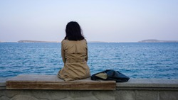 Young sad depressed woman sit alone on bench, looking at distant sea / seascape horizon. Time to go, say goodbye. Miss someone. Desire, hope to go far away. Unhappy girl feel lonely at seaside outdoor