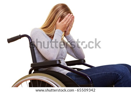 Young sad disabled woman in wheelchair crying