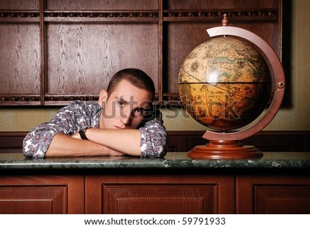 young sad handsome man at  bar counter near the global map