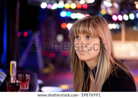 young sad woman in a discotheque