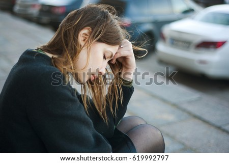 Young sad woman sitting on the stairs in the street