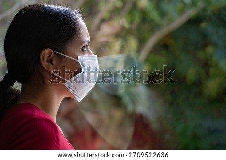 Young sad woman wearing a face mask looking through the window with her reflection on the glass, self isolated at home. Coronavirus and Quarentine concept