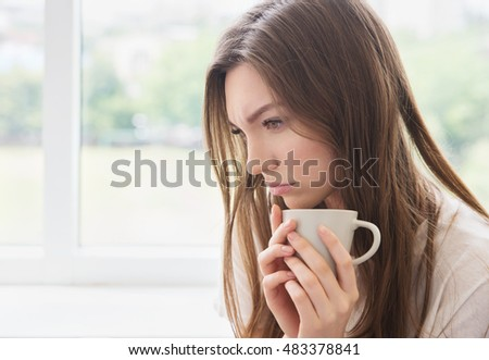 Young sad woman with cup of coffee or tea. Stress, depression, illness concept.