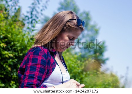 Young sad woman with short brown hair wearing plaid shirt looking down at her hands on a sunny day – Casually dressed millennial feeling depressed in nature #1424287172